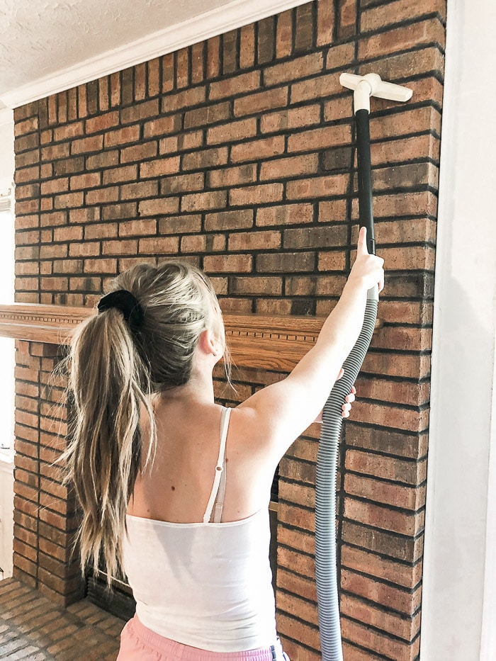 How to paint fireplace bricks beginning with cleaning the bricks with a vacuum.