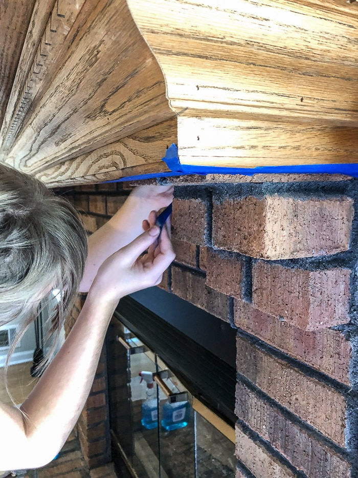 How to paint fireplace bricks.  After cleaning the bricks tape off anything you do not want paint to get on.