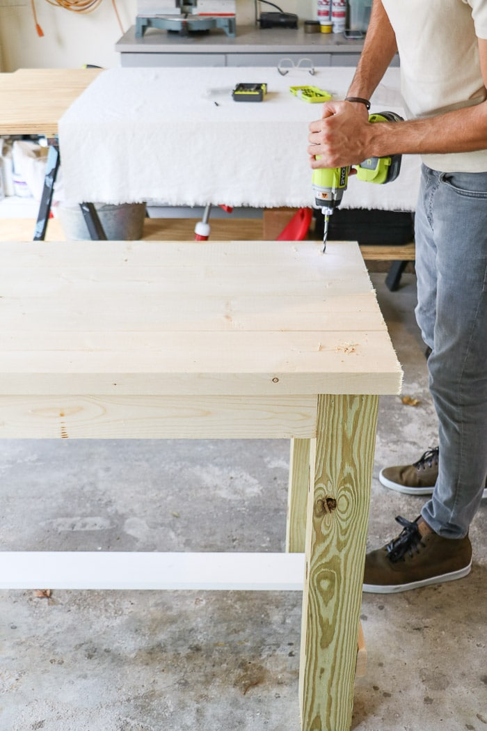 How to build a farmhouse table. Drill hole for screws to go into the legs from the top of the table.
