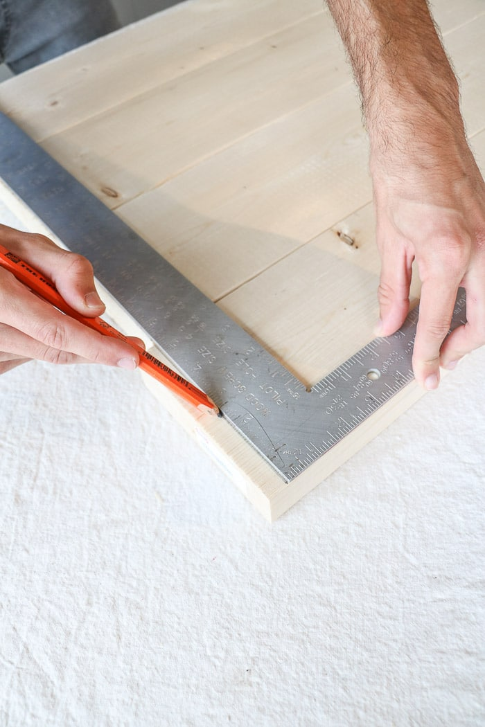 How to build a farmhouse table. Use a L shaped measuring tool to draw a line to cut the boards.