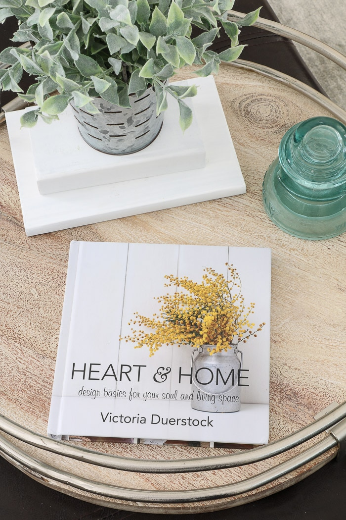 Heart and Home is one of the best interior design books for beginners.  This home decor book and devotional has flowers on the cover and it is sitting with an old insulator, chalk painted books and greenery.