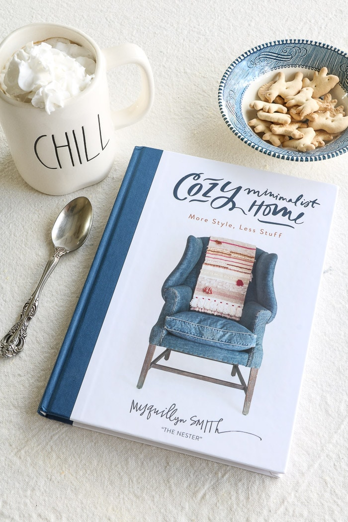 Cozy Minimalist Home by Myquillyn Smith.  One of the best interior design books for beginners.  A warm cup of coffee filled with cream and a bowl of cookies.