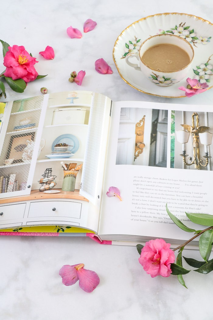 Inside of the book Whiskey in a Teacup by Reese Witherspoon along with a floral china teacup filled with warm coffee and rose colored gardenia flowers and petal sprinkled all around the book.  This is easy one of the best interior design books for beginners.