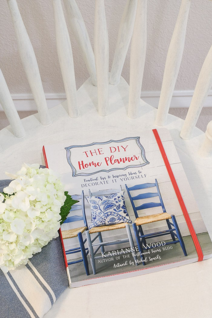 The DIY Home Planner by KariAnne Wood and a magnolia flower.  One of the best interior design books for beginners.