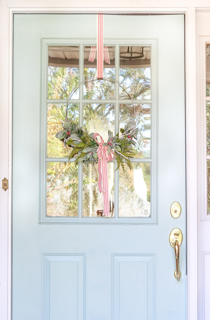 Minimalist Christmas wreath hanging with a ribbon on a front door.