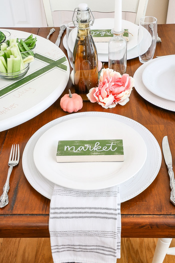 Dollar Tree fall decorating ideas for a Thanksgiving tablescape using a cute market sign for a place setting centerpiece.  Stacked white dishes with a decorative dish towel between the dishes and a white painted charger.