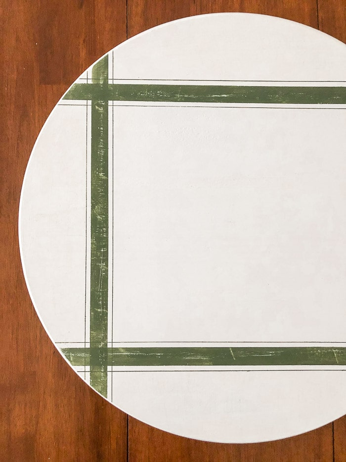 White oversized lazy susan with grain cloth stripes in green on it and distressed with a clear chalkboard finish on the top.
