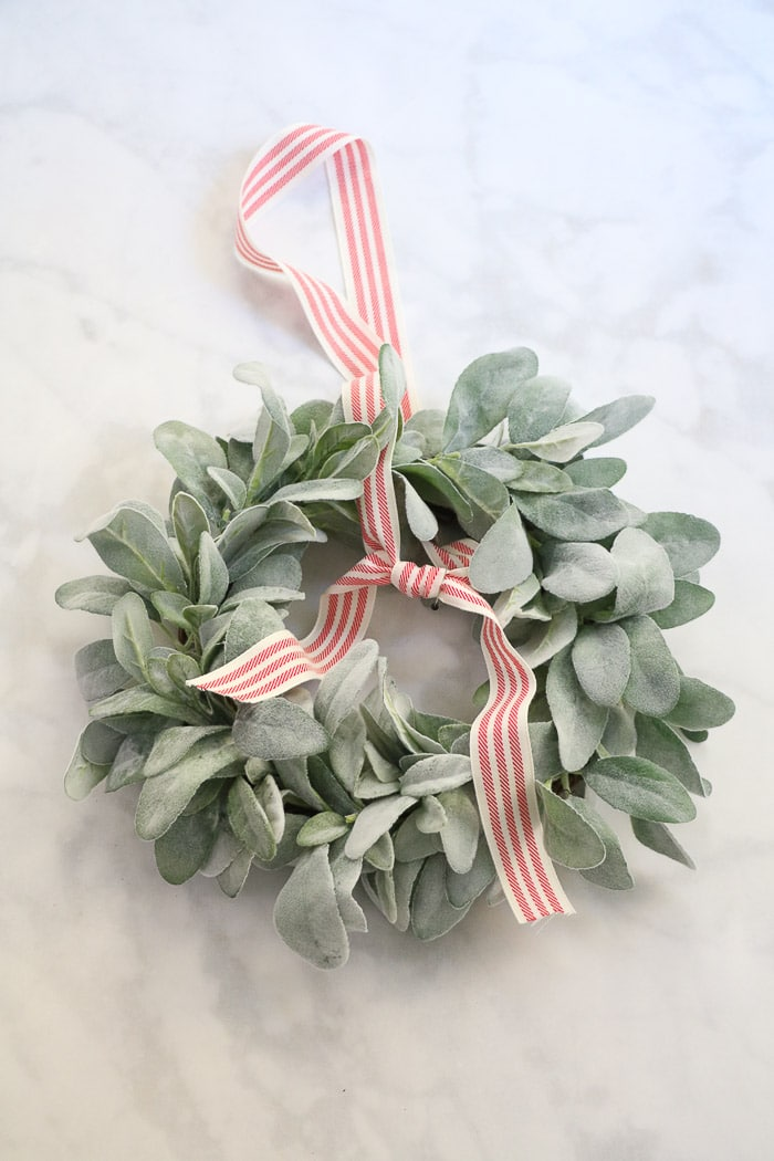 How to hang a wreath with ribbon on a window.  This simple DIY will show you two ways to hang wreaths on windows inside your home.  On this step tie the ribbon in a sailors knot where you marked with a pin.