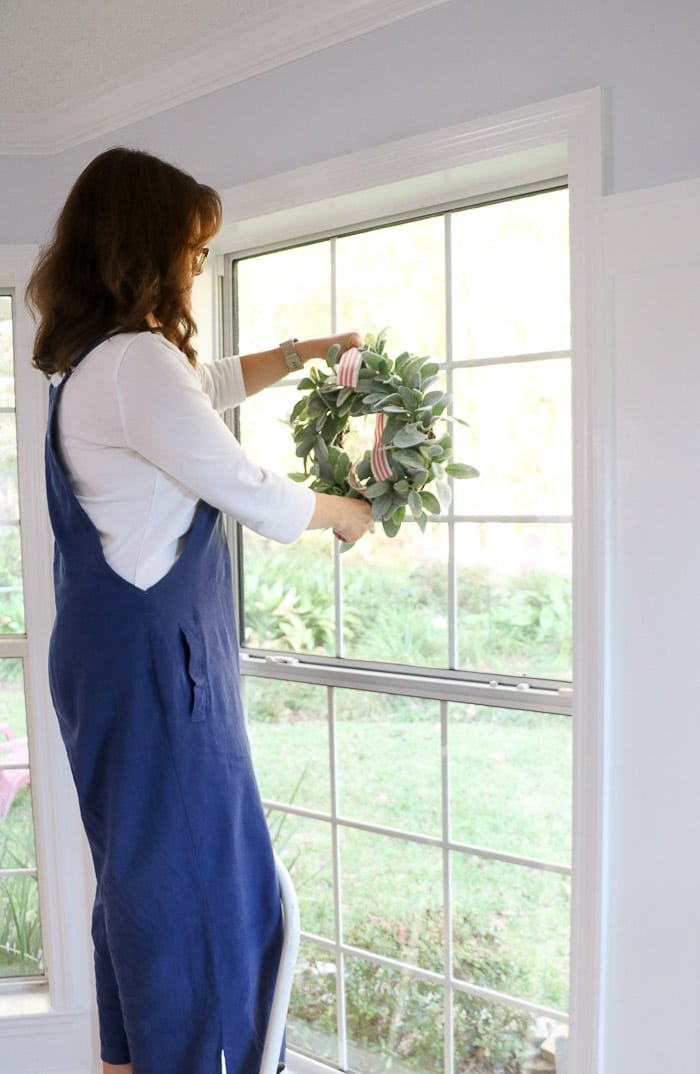How to hang a wreath with ribbon on a window.  This simple DIY will show you two ways to hang wreaths on windows inside your home.  On this step hang the wreath on the hook.