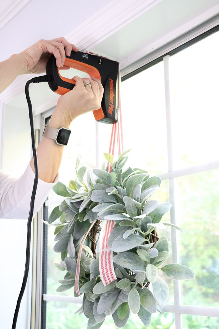 How to hang a wreath with ribbon on a window.  This simple DIY will show you two ways to hang wreaths on windows inside your home.  Another option for hanging your wreath is to use a staple gun and adhere it to the top of the window seal.