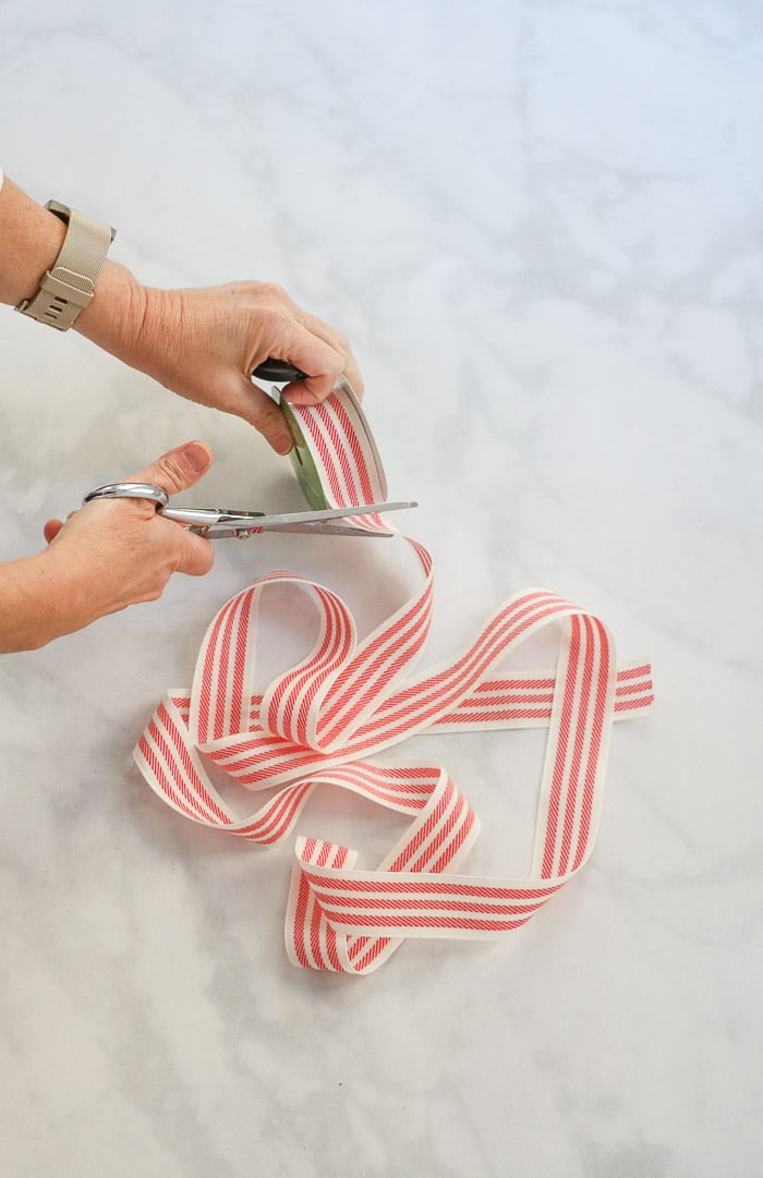 How to hang a wreath with ribbon on a window.  This simple DIY will show you two ways to hang wreaths on windows inside your home.  Start by measuring and cutting your ribbon.