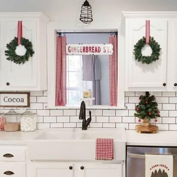 Christmas Kitchen Decor by Our Cozy Cottage with wreaths hanging on cabinets and red and white plaid