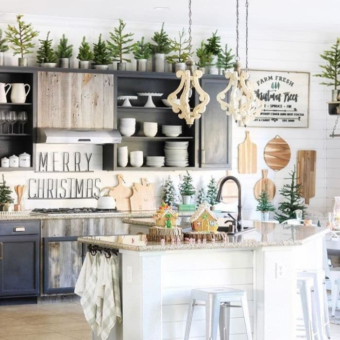Christmas Kitchen Decor by I Dream of Homemaking with mini Christmas trees on top of cupboards and sprinkled around the countertops