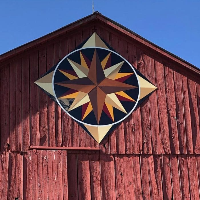 Decorating With Barn Quilts by 100 Acres Of with a barn quilt hanging on a barn