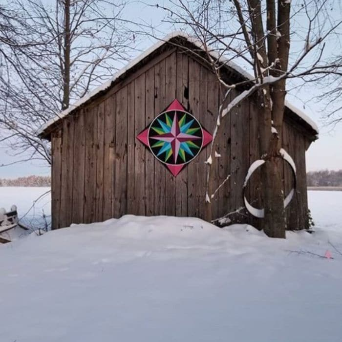 Decorating With Barn Quilts by Gardiners Gate with a barn quilt adorning a wooden barn in the snow