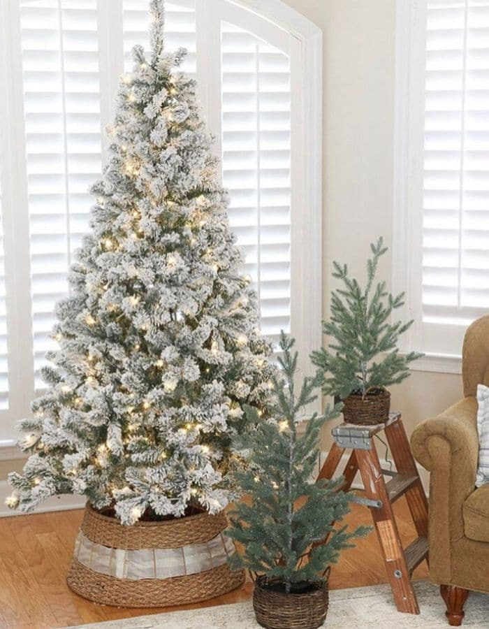 Christmas Tree Base Ideas with a flocked artificial tree surrounded by a woven basket tree collar and laced with a white ribbon