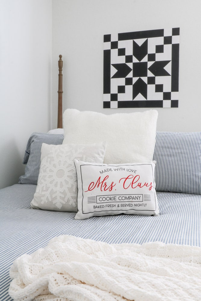 "Barn quilt hanging over a bed in a white room with a blue and white strip bedding and a pillows in white, snowflake and a ""made with love Mrs. Claus cookie company"" pillow."