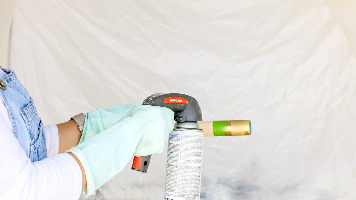 DIY life size nutcracker by taping the ends of a wooden dowel and spray painting it gold for the arms.