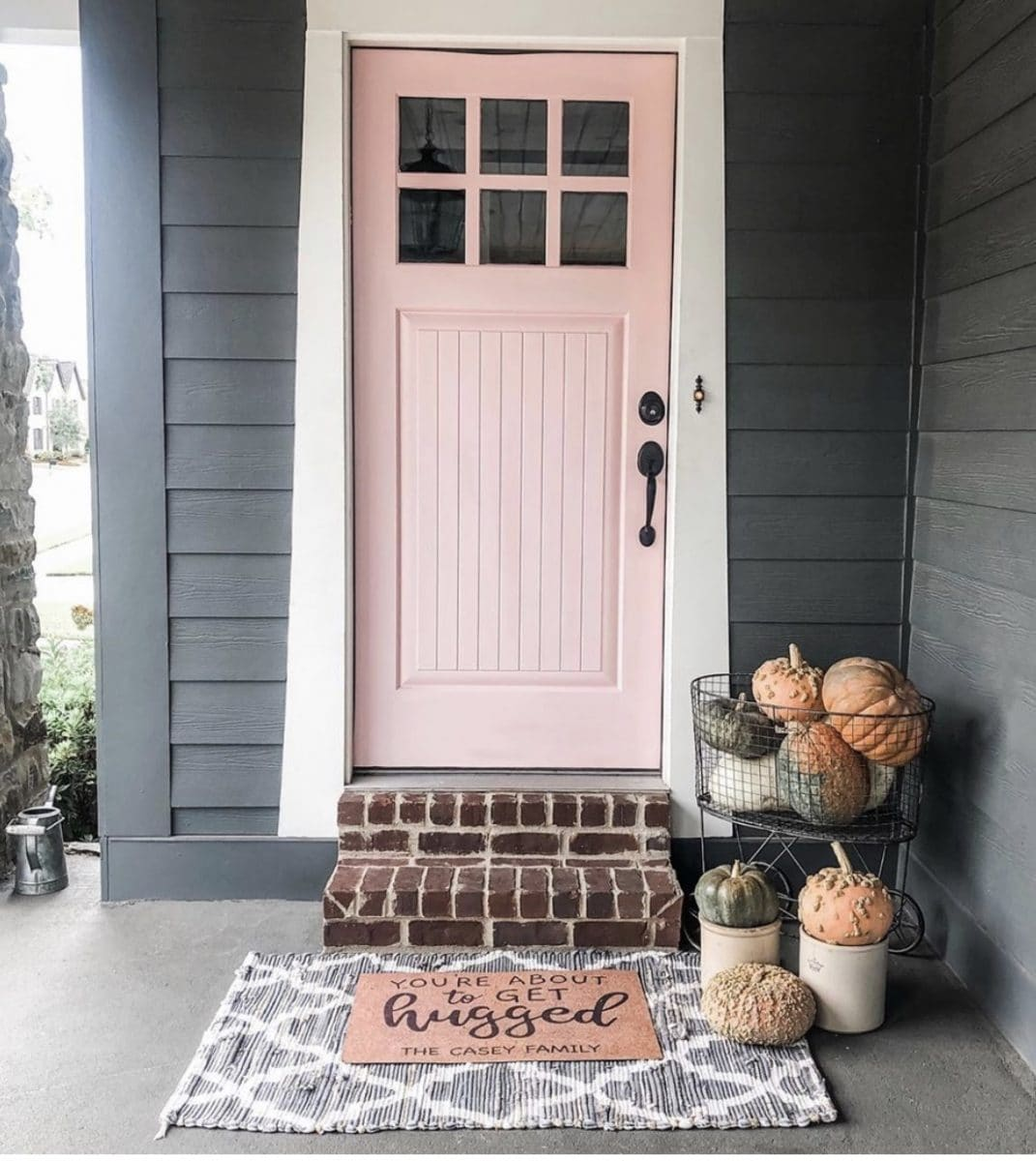 Pink paint color on a modern front door.  Shaker style door in Loveable paint color by Sherwin Williams on a grey house with white trim.