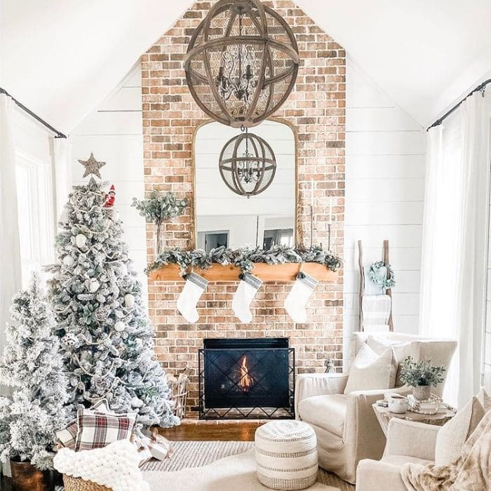 White Christmas Tree Ideas by Between White Houses with a white decorated Christmas tree next to a brick fireplace