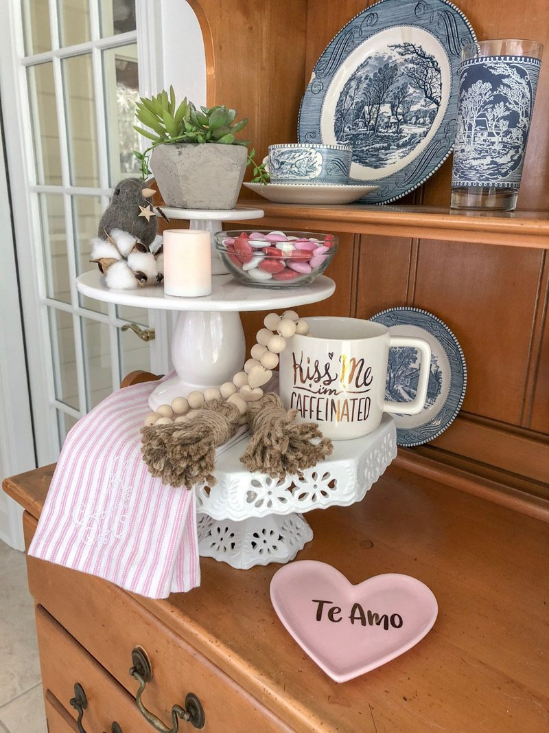 Styling tiered trays with cake stands layered and filled with Valentine decor,