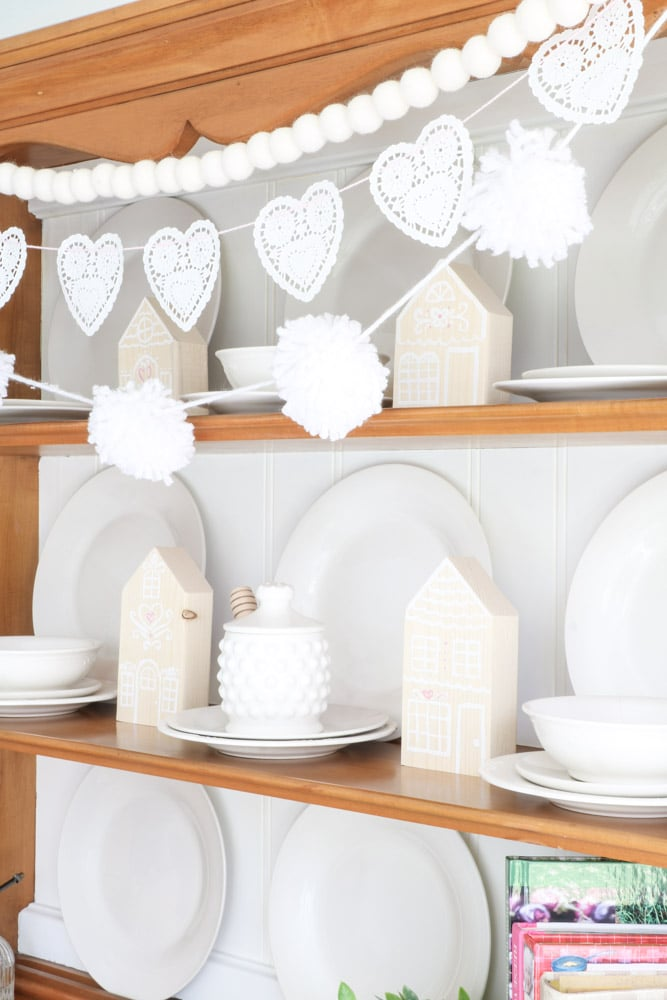 Decorate for Valentine with wooden gingerbread houses nestled on a hutch and garland of heart shaped doilies, felt ball garland and yarn ball garland all in white.