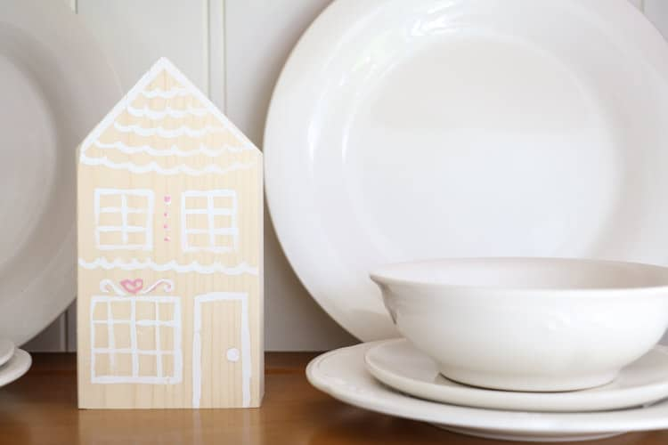 decorate for Valentine with these wooden gingerbread houses nestled between dishes in a hutch