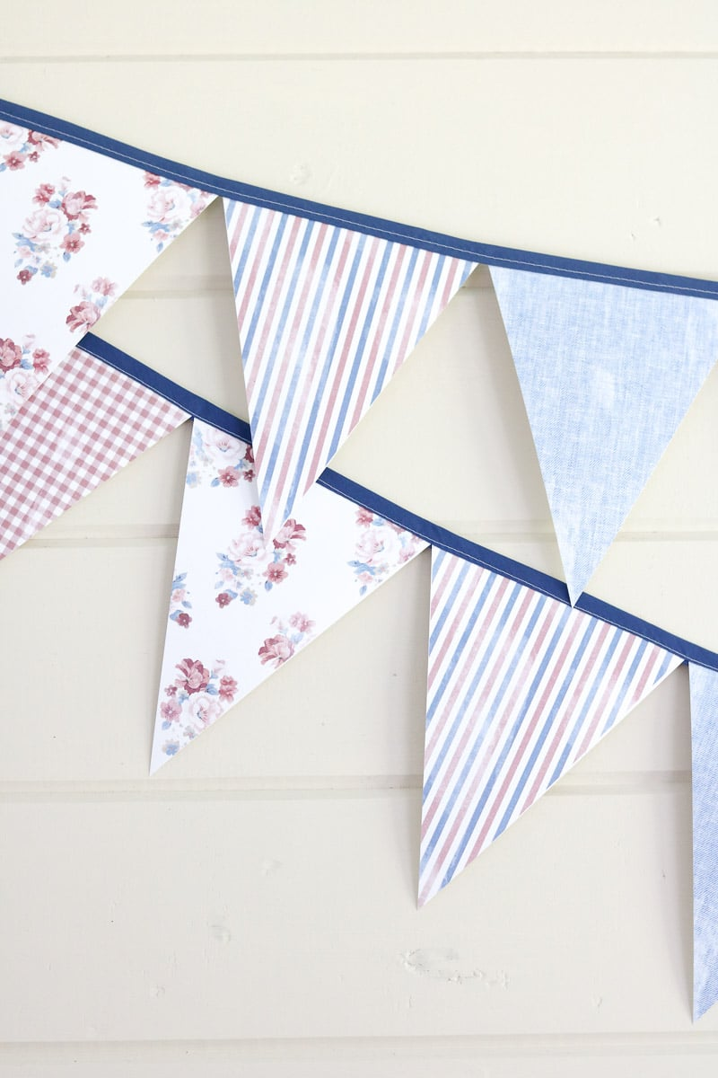 Free printable banner in distressed fabric patterns of chambray, red and white stripes, floral pattern and red and white gingham.