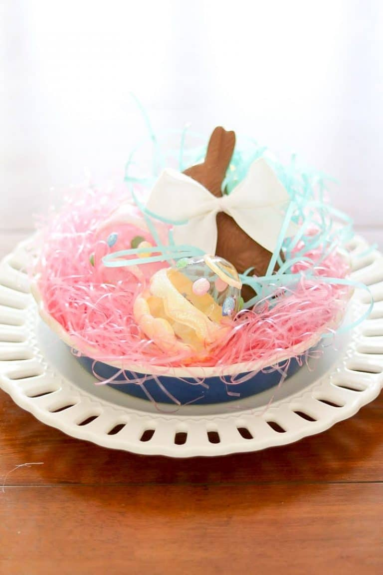 Easter centerpiece of layered dishes, bright colored grass, chocolate bunny, glass eggs.
