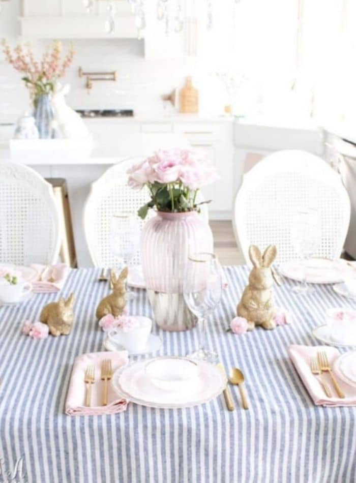 Easter tablescape using striped blue and white fabric, gold bunnies, pink glass vase full of pink roses and created by Summer Adams