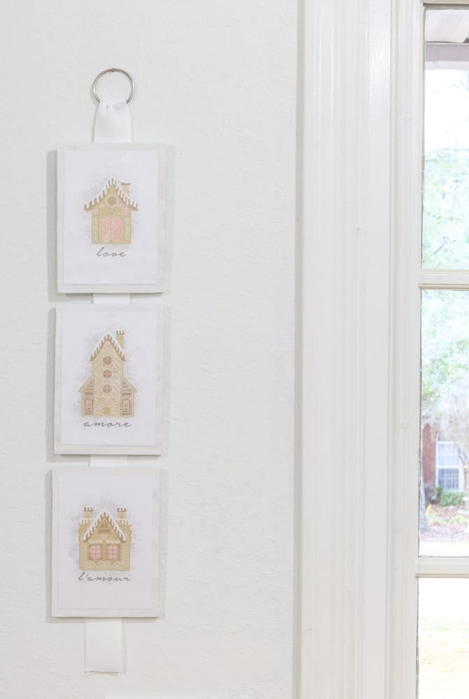 Three gingerbread printables attached to wood and hung by ribbon for decoration.