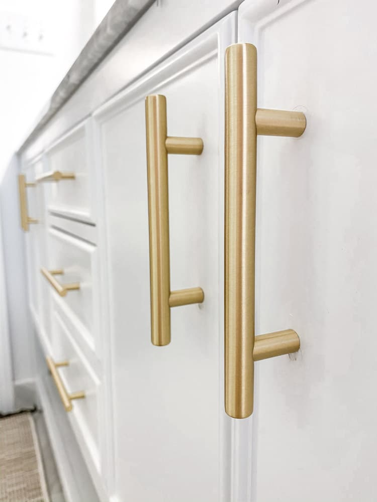 Small farmhouse bathroom remodel using Emtek brushed brass cabinet bar pulls.