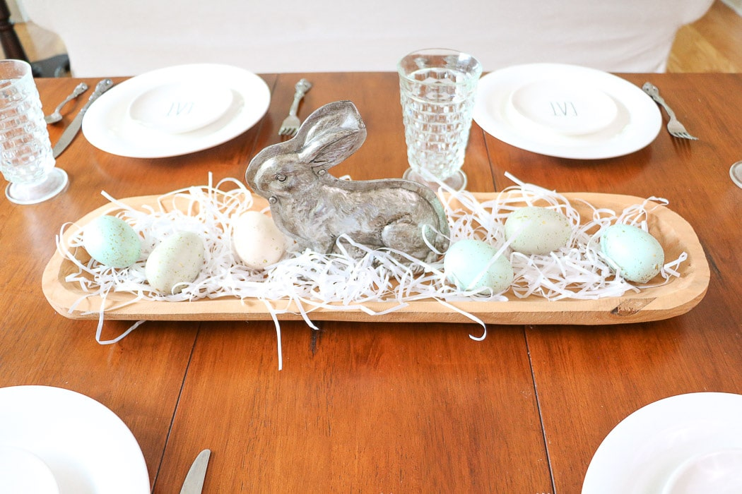 Easter centerpiece of a dough bowl filled with white grass, speckled eggs and a silver bunny mold in the middle.  And Rae Dunn Easter place settings.