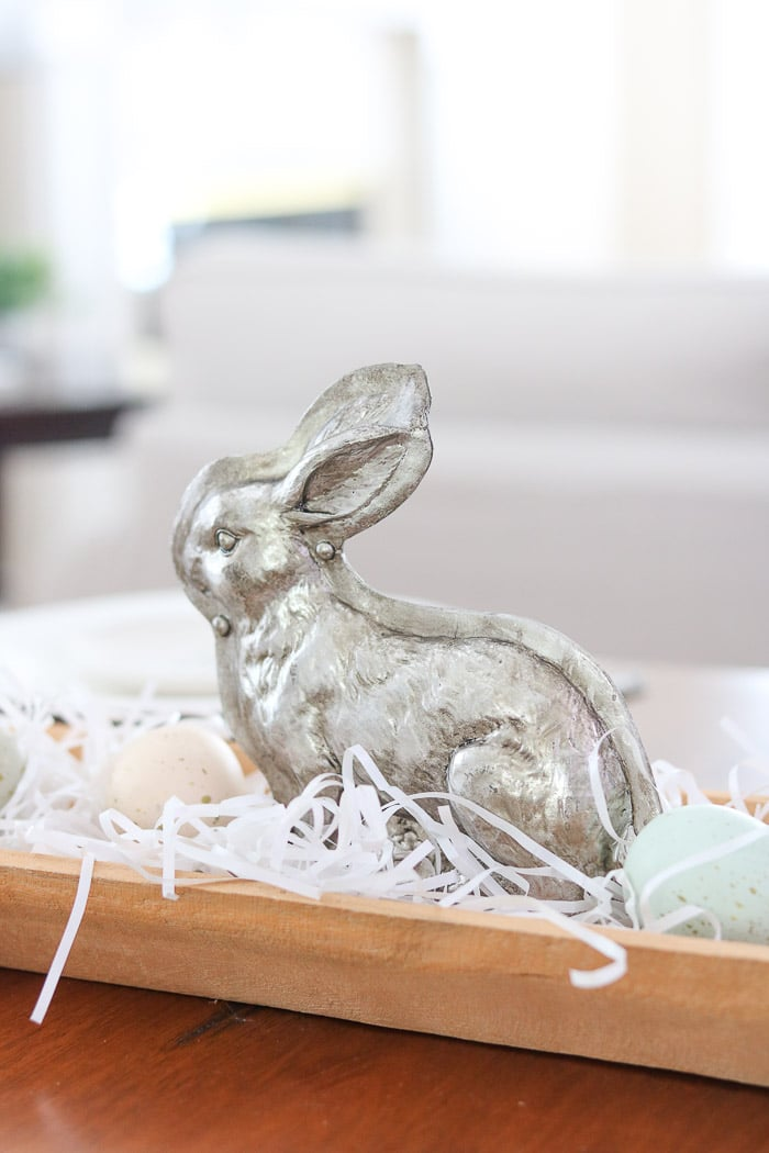 Easter centerpiece of a dough bowl filled with white grass, speckled eggs and a silver bunny mold in the middle.