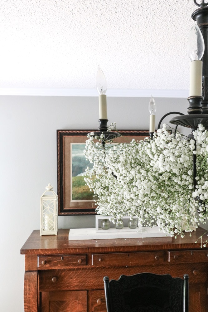 Chandelier decorated with baby's breath flowers in a dining room.
