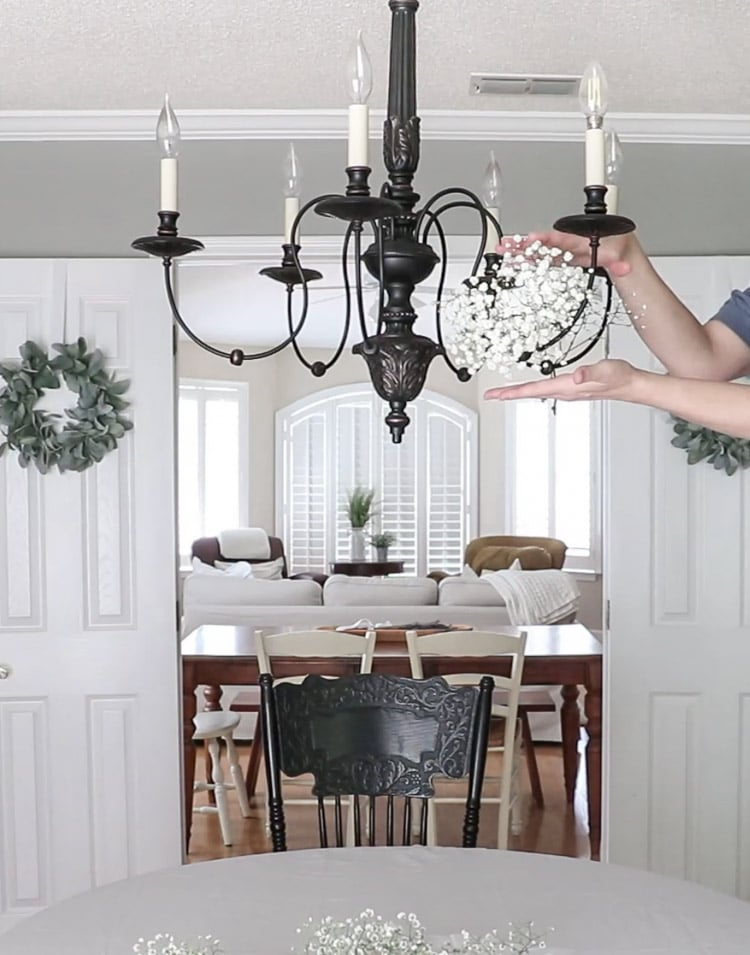 Lay a stem of baby's breath on one arm of the chandelier
