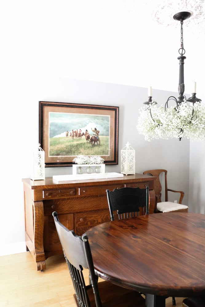 Decorate a chandelier with baby's breath flowers in a dining room.