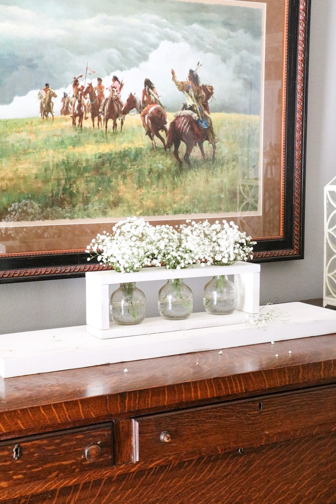 Baby's breath flowers arrangement into a wooden framed vase holder on a buffet in a dining room.