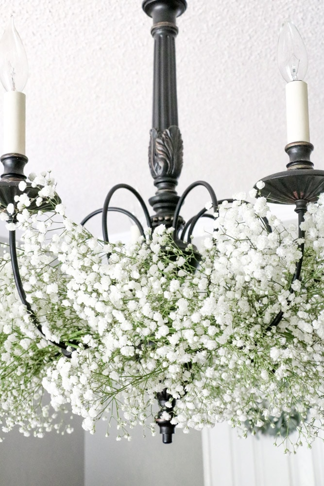 Decorate a chandelier with baby's breath flowers.