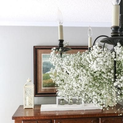 Black chandelier decorated with baby's breath flowers in a dining room.