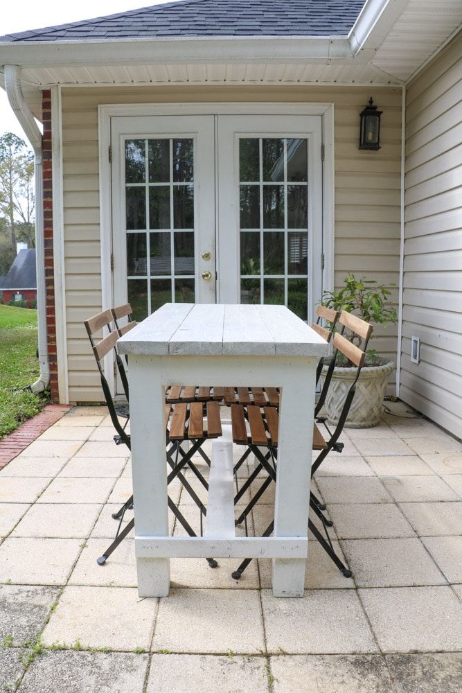 Farmhouse table and french folding bistro chairs on a back patio.