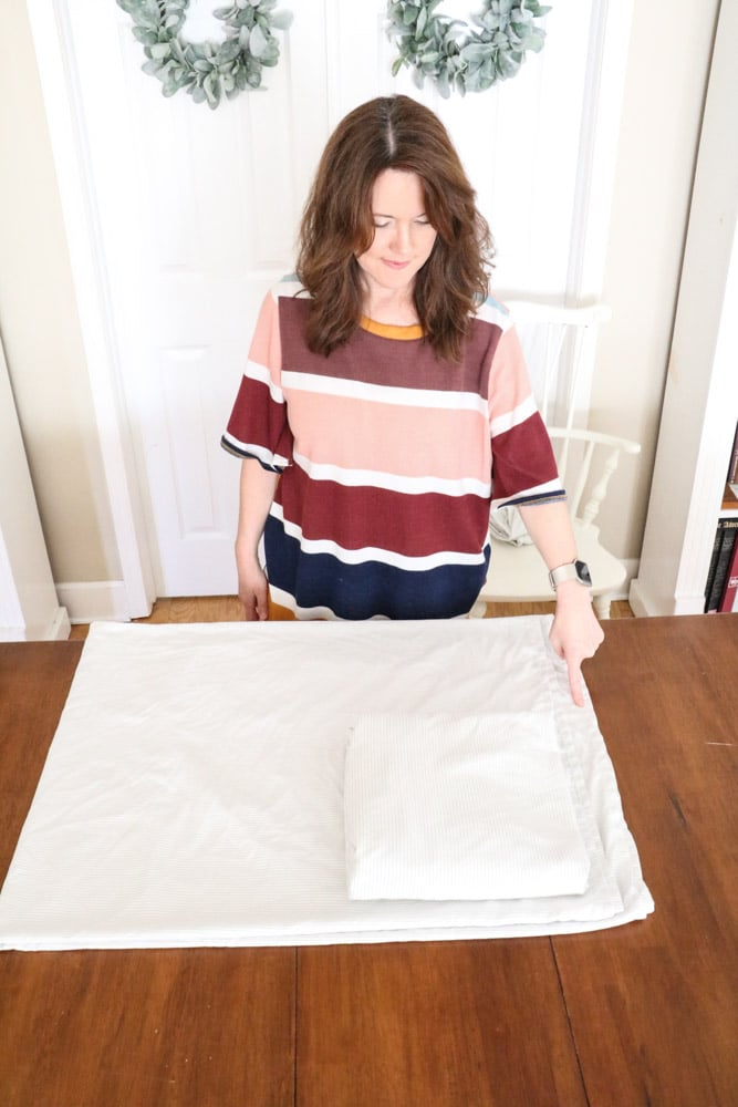 How to fold bed sheets neatly by placing the folded fitted sheet into the corner of the flat sheet.