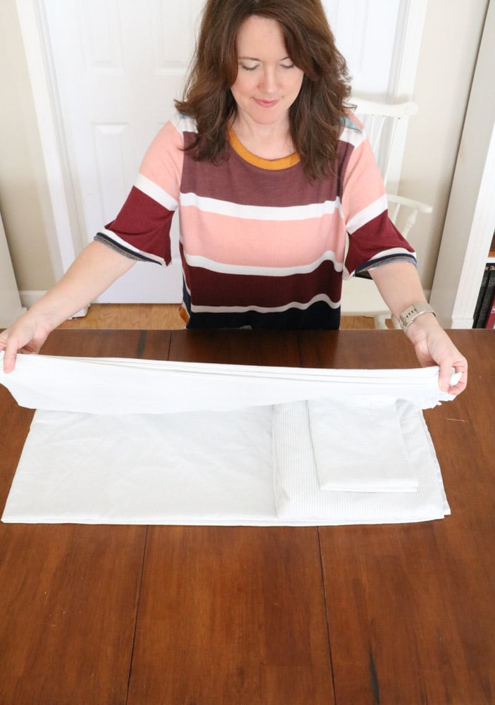 How to fold bed sheets neatly by folding the flat sheet over the fitted sheet and pillowcase.