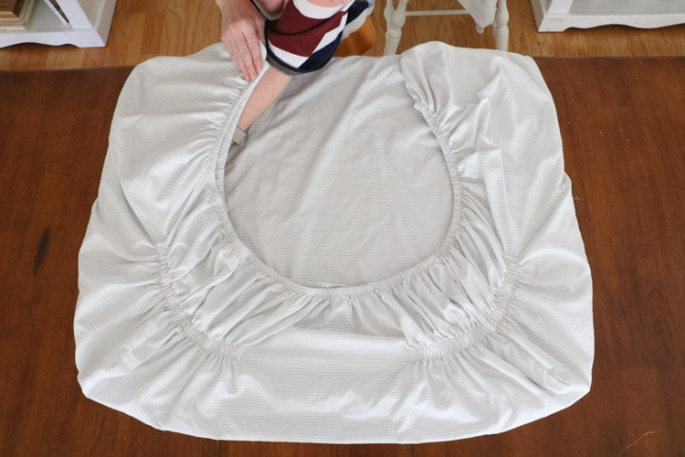 How to fold bed sheets neatly by laying the corners down on the table and making a square.