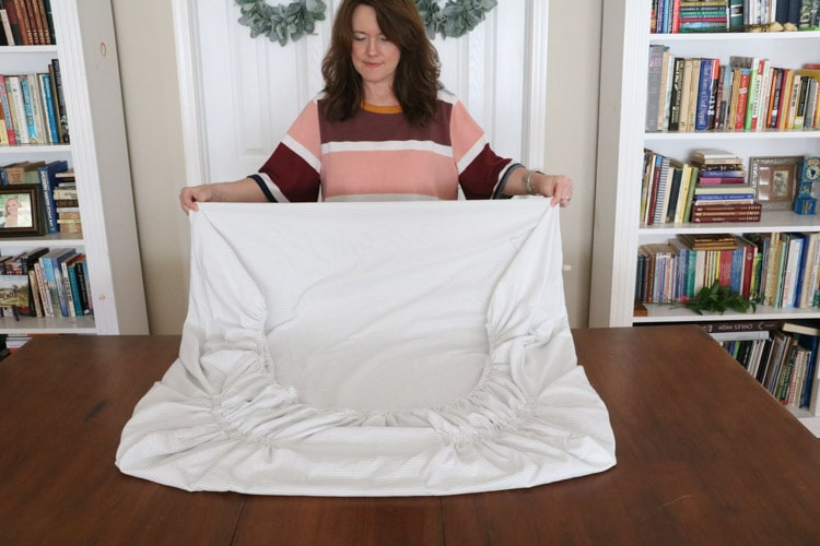 How to fold bed sheets neatly by grabbing the other end of the square and folding it over.