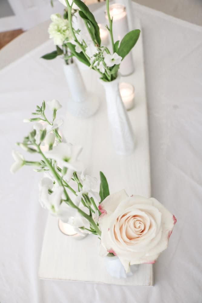 Bridal shower centerpiece of milk glass vases filled with flowers and candles.
