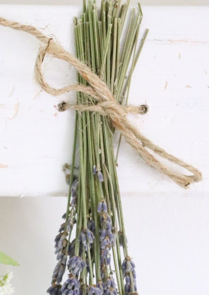Dried flower wall hanging with lavender tied to a wood board.