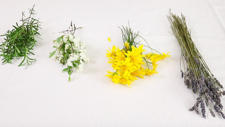 Dried flower hanging DIY with rosemary, white bridal spirea, daisy bush flowers and lavender bouquets sitting on a table.