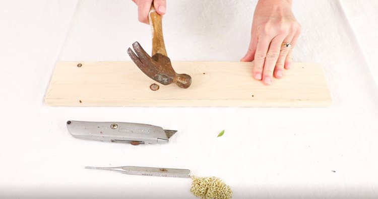 Dried flower wall hanger project beginning by distressing a board with a hammer.