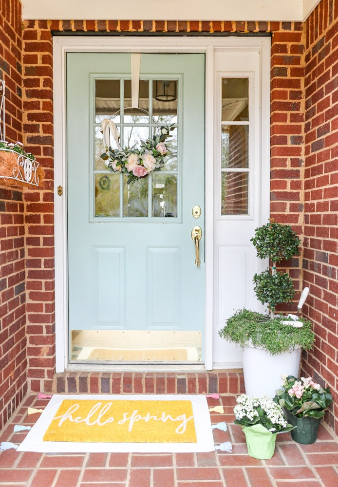 Front porch decorated for spring and a layered rug with a drop cloth rug with tassels